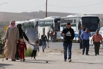 People walk as they wait to travel to Syria at Jordan's Jaber border crossing, near Syria's Nassib checkpoint, near Mafraq