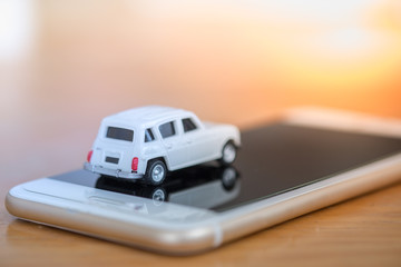Transport, Technology and Travel concept. Close up of miniature car toy on smart phone on woode table.