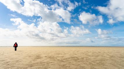 Spaziergängerin am Sandstrand mit Wolken