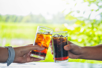Men and Woman hand giving glass of cola.Glass of cola ,Soft drinks with ice, sweetheart or buddy