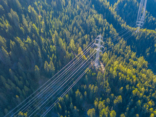 Aerial view of power line pylon in mountaineous area in Switzerland through valley in Canton of Valais