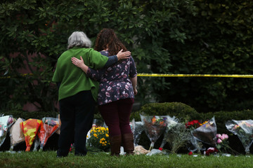 People visit an impromptu memorial at the Tree of Life synagogue following Saturday's shooting at the synagogue in Pittsburgh Pennsylvania