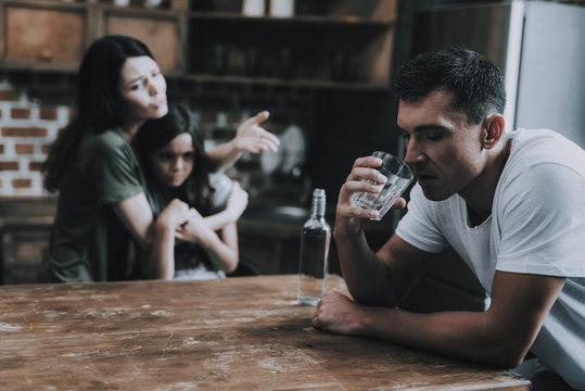 Wife and Kid Look at Father Getting Drunk at Home