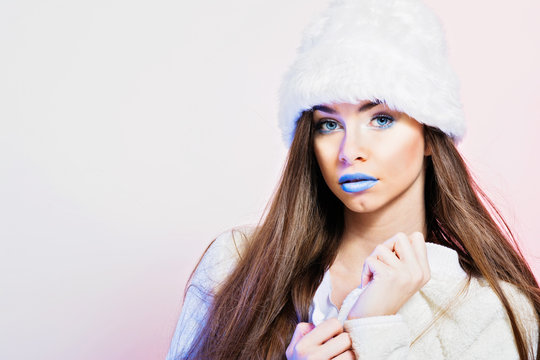 Gorgeous young woman in white winter outfit, with blue lips and eyes, posing. Studio lighting, closeup, retouched.