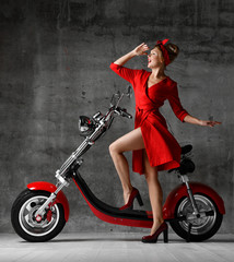 Woman ride sit on motorcycle bicycle scooter pinup retro style laughing smiling red dress