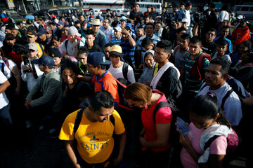 People pray before departing with a caravan of migrants from El Salvador en route to the United States, in San Salvador