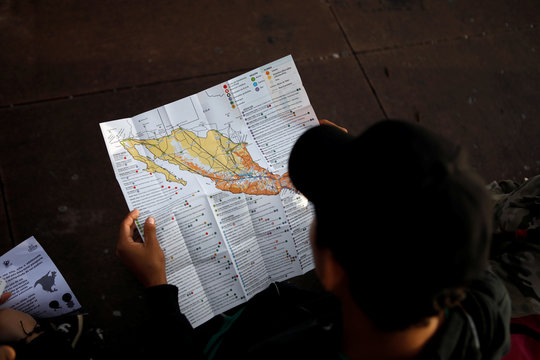 A man watches a map of Mexico before departing with a caravan of migrants from El Salvador en route to the United States, in San Salvador