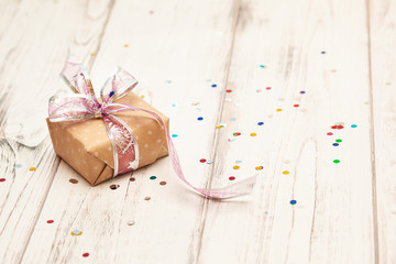 brown gift box with ribbon  on white wooden board background with confetti. Selective focus