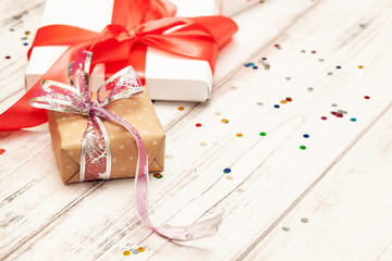 Gift boxex with thin red ribbon and confetti on old white wood table. Selective focus