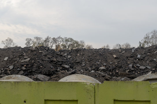 The garbage in the form of a mountain of old broken asphalt.
