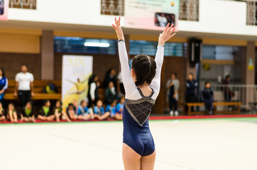 Little gymnast waving to the public in a competition at the stadium