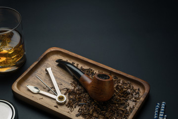 a smoking pipe with tobacco and a tamper tool in wooden tray, a glass of bourbon whiskey and pipe cleaners on the black table