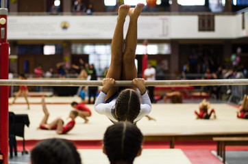 Athletic little girl gymnast performing exercises at the bar in the championship