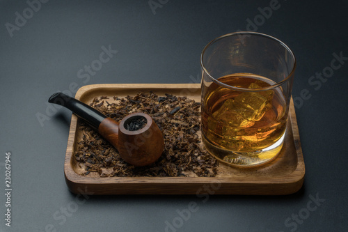 a smoking pipe with tobacco and a glass of bourbon whiskey in wooden