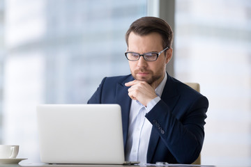 Caucasian man sitting at the table near laptop in the office and looking at the screen. Serious and pensive boss or employee working at his workplace and feeling interest or analyzing results.