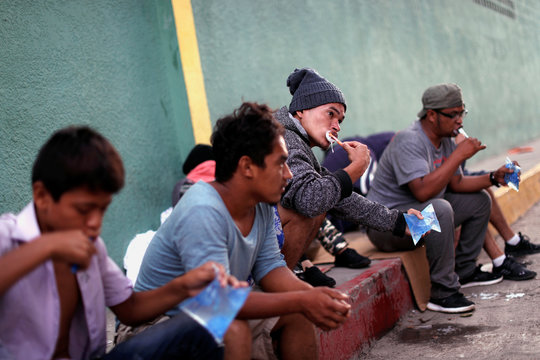 Central Americans, part of a caravan trying to reach the U.S., brush their teeth before trying to cross the border into Mexico and carry on their journey, in Tecun Uman