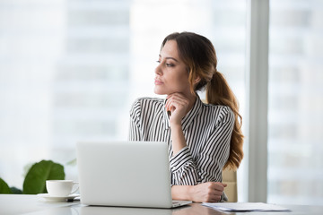 Focused pensive young woman looking in distance in window. Businesswoman at workplace behind laptop. challenging work, task, thinking about strategy, business projects. Business vision concept