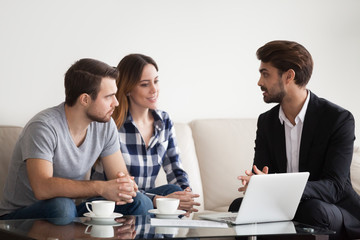 Young couple, family at meeting with realtor, interior designer, decorator, landlord. Employee consulting, showing sketches on laptop. Concept of meeting with client, customer.
