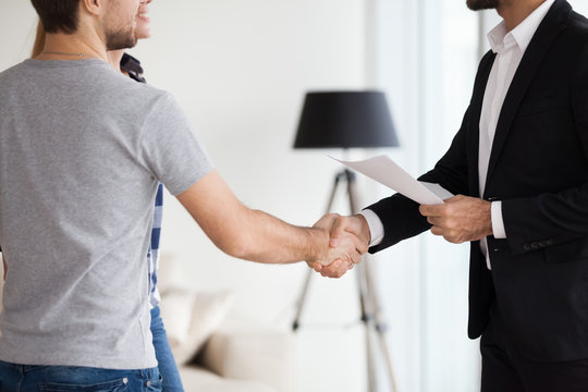 Young couple, family at meeting making deal, signing ontract with realtor, landlord, banker. Husband handshaking with man in suit. Concept of meeting with client, customer. Closes up