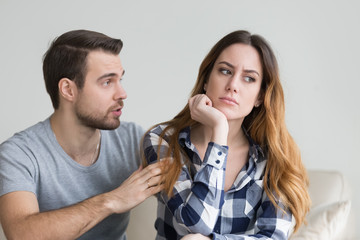Wife offended by husband, man asks for forgiveness. Angry depressed young woman has no desire to talk, listening to lies of her boyfriend saying sorry. Troubles in family, misunderstanding, distrust