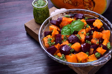 Roasted pieces of pumpkin and beetroot with pesto sauce in a glass dish. Vegetarian meal