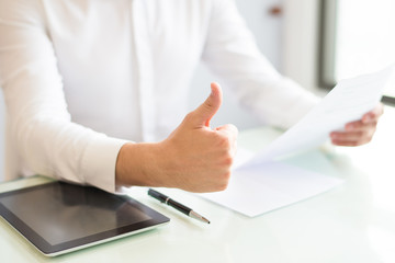 Closeup of man holding document and showing thumb up. Entrepreneur sitting at desk and working. Success and contract concept. Cropped view.