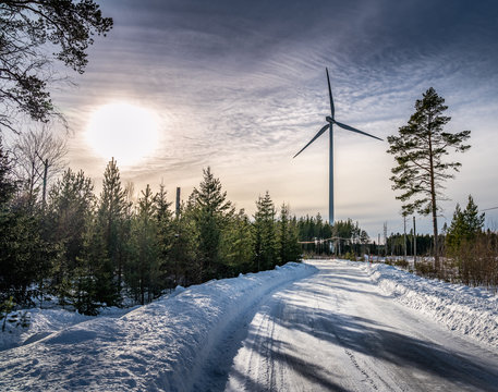 photo of windmill and curvy road in winter pine tree forest, blue sky, foggy winter sun, Sweden