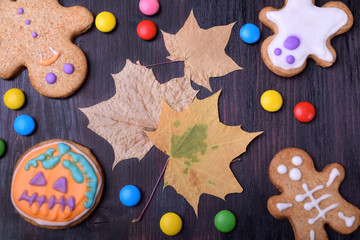 Halloween gingerbread cookies decorated with multicoloured glazing and dry maple leaves against the dark background