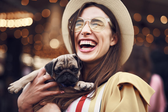 Cheerful happy young long haired lady holing adorable puppy and closing her eyes while laughing