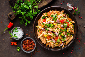 Spicy pasta penne bolognese with vegetables, beans, chili and cheese in tomato sauce