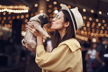 Kissing puppy. Happy young pretty lady standing outdoors with hat on her head and kissing cute puppy in her hands Wall mural