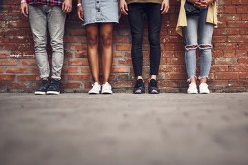 Legs of friends. Horizontal image of four stylish people standing next to the brick wall and posing for the photo