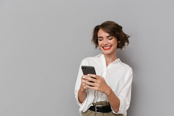 Wall Mural - Photo of caucasian woman 20s smiling and holding mobile phone, isolated over gray background