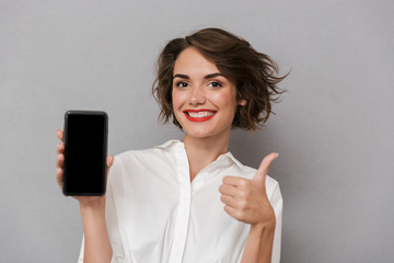 Wall Mural - Photo of beautiful woman 20s holding mobile phone and showing copyspace screen, isolated over gray background
