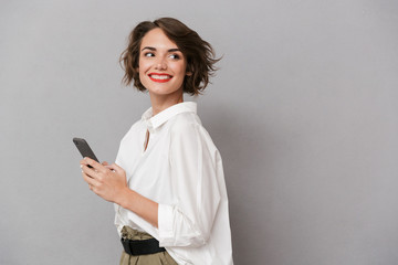 Photo of attractive woman 20s smiling and holding mobile phone, isolated over gray background