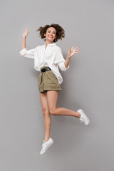 Wall Mural - Full length image of european woman 20s smiling and jumping, isolated over gray background