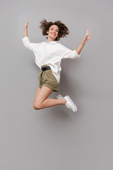 Wall Mural - Full length image of positive girl 20s smiling and jumping, isolated over gray background