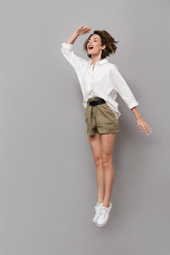 Full length image of caucasian woman 20s smiling and jumping, isolated over gray background