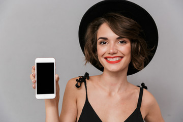 Wall Mural - Photo of gorgeous woman 20s wearing black dress and hat holding smartphone, isolated over gray background