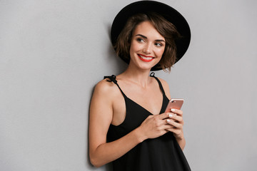 Photo of attractive woman 20s wearing black dress and hat smiling at camera while holding smartphone, isolated over gray background