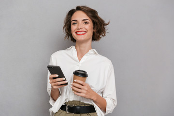 Wall Mural - Photo of pleased woman 20s holding takeaway coffee and using mobile phone, isolated over gray background