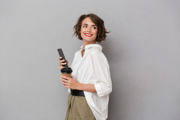 Wall Mural - Photo of positive woman 20s holding takeaway coffee and using mobile phone, isolated over gray background