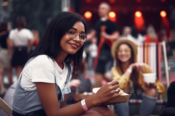 Portrait of beautiful young lady in glasses holding food and looking at camera with smile. Stage and people on blurred background