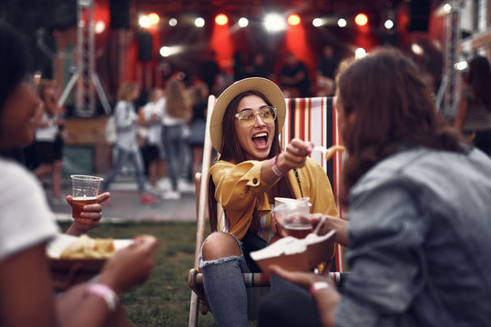 Portrait of smiling young lady in hat sitting on folding chair and letting boyfriend taste french fry. Young people resting during outdoor concert