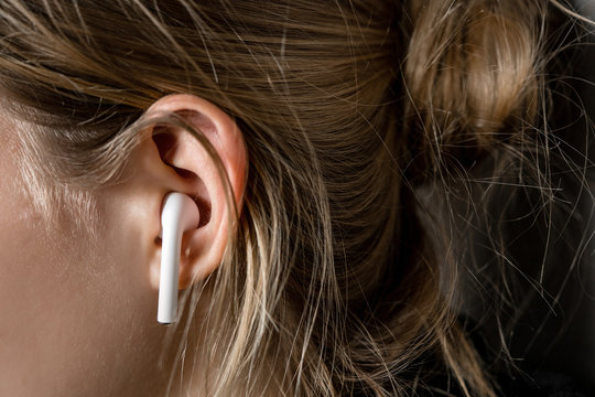 Earphone wireless white in the ear of a young girl. Modern Technologies and Music.