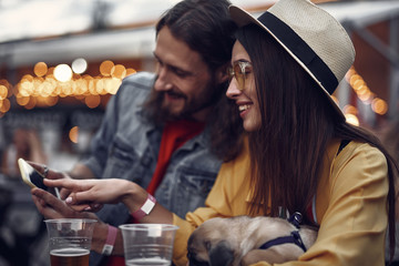 Side view portrait of hipster young lady in hat pointing at display of cellphone and smiling. She is sitting at the table with bearded man and holding cute pug dog
