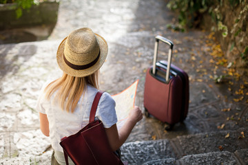 Girl traveler with suitcase is sitting on stone stairs in autumn. Young woman tourist is searching direction at town streets. Concept of travel, vacation, female tourism, adventure, trip, journey.