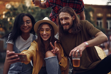 Portrait of stylish hipster friends sitting on car and taking picture with smartphone. Lovely girl in hat showing victory sign while smiling bearded guy holding beer