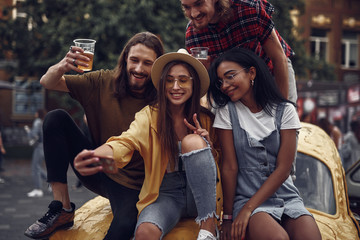 Portrait of stylish young people sitting on car and taking picture with smartphone. Smiling bearded guys holding cups with cold beer