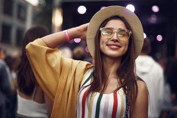 Portrait of charming girl touching hat and looking away with smile. Crowd on blurred background